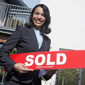 Realtor Holding Sign Home Sold Subject to Contract