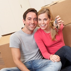 young couple with condo keys moving in