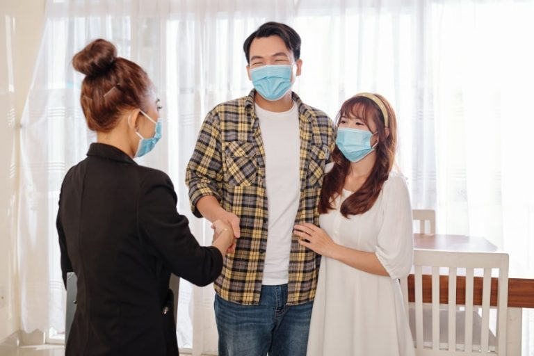 Real estate agent meets with couple wearing masks